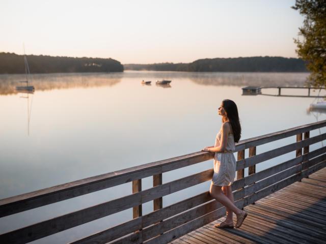 Une jeune femme au lever du soleil sur le lac de Trémelin