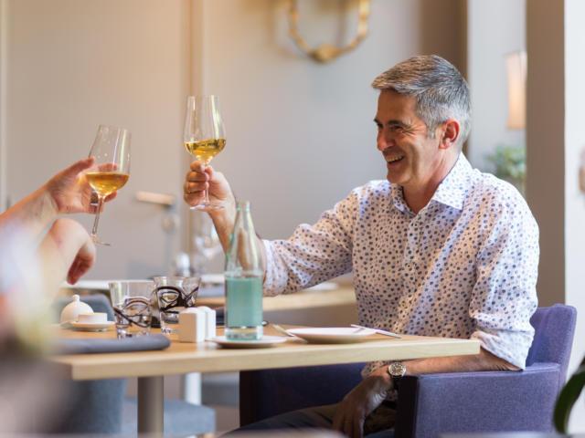 Homme portant un toast au restaurant