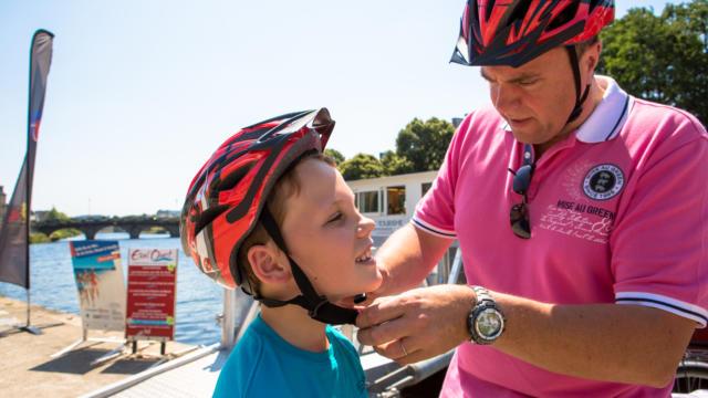 Le papa attache le casque de son fils sur la Vélodyssée
